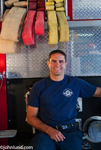 Picture of a happy smiling Hispanic fireman leaning against fire engine and wearing a blue T shirt. A number of fire hoses of different sizes and colors are hanging over his head. The fireman has short hair and rugged good looks.